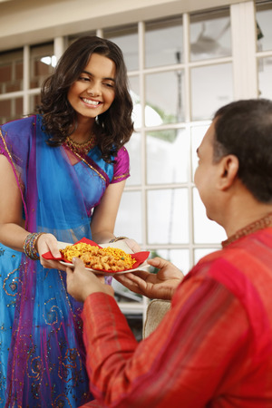 Teenage girl serving man with a plate of Indian snacks