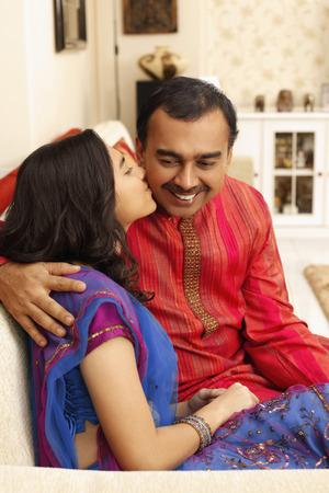 kurta: Teenage girl giving man a peck on his cheek