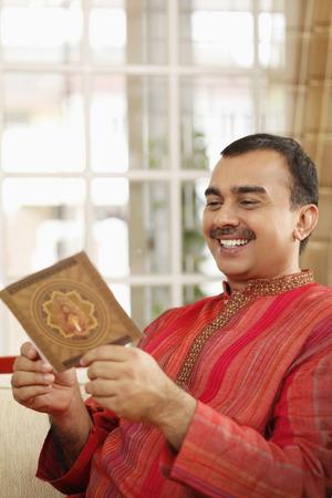 kurta: Man smiling while reading greeting card