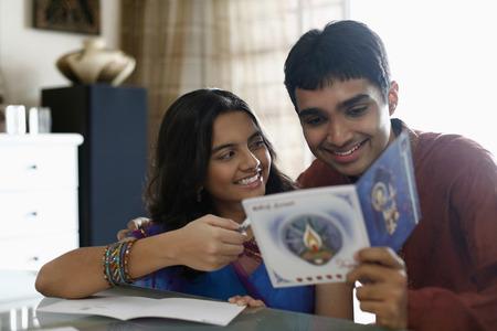 kurta: Teenage girl and young man reading greeting card together