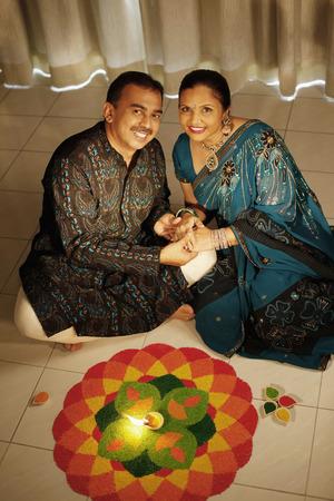 kurta: Man and woman holding hands while sitting next to kolam LANG_EVOIMAGES
