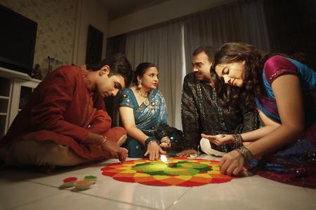 kurta: Family drawing kolam on the floor