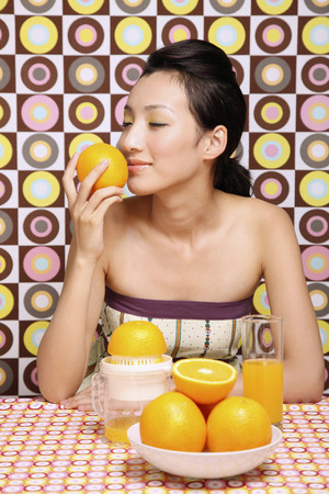 smelling: Woman smelling orange