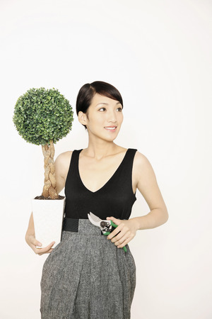 potted plant: Woman with potted plant and pruning shears LANG_EVOIMAGES