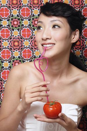 Woman enjoying tomato juice LANG_EVOIMAGES