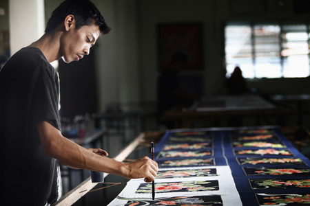 Man painting batik fabric Stock Photo