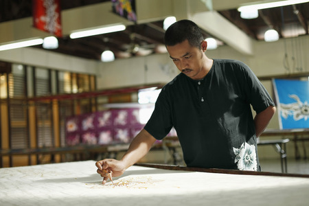 Man drawing batik patterns on fabric Stock Photo