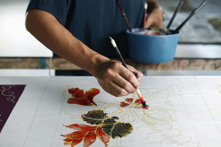fabric painting: Man painting batik fabric LANG_EVOIMAGES