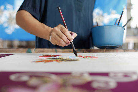 Man painting batik fabric LANG_EVOIMAGES