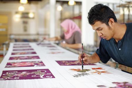 Man and woman painting batik fabric