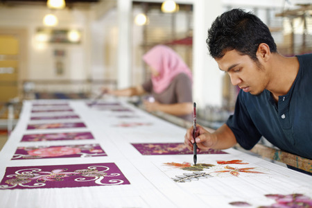 Man and woman painting batik fabric