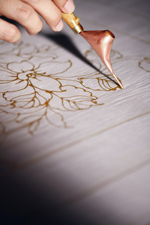 Man drawing batik patterns on fabric Foto de archivo