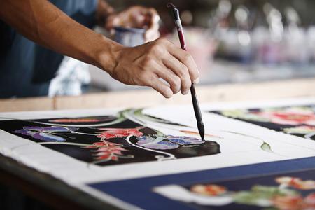 Man painting batik fabric Imagens
