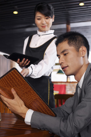 recommending: Businessman reading menu, waitress recommending some dishes