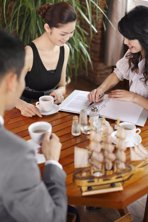 Businesswomen reading document together, businessman enjoying a cup of coffee