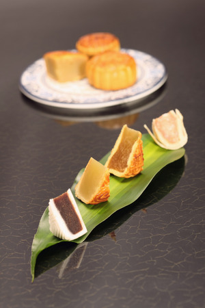 five objects: Variant of cut mooncakes on a leaf