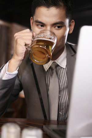 necktie beer: Businessman enjoying a glass of beer while using laptop LANG_EVOIMAGES