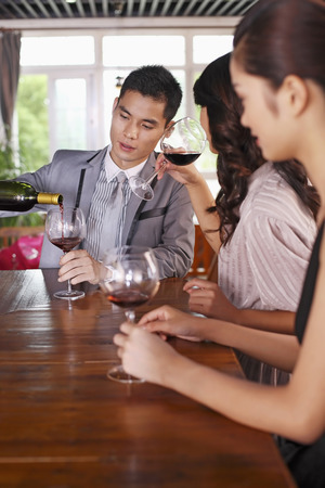 only three people: Businessman pouring red wine for businesswomen LANG_EVOIMAGES