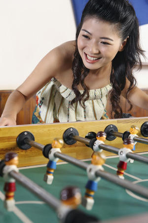 foosball: Woman playing foosball