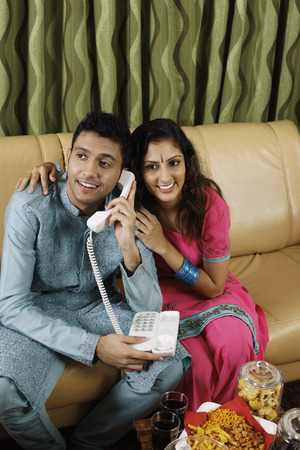 salwar: Man talking on the phone, woman trying to listen to the conversation LANG_EVOIMAGES