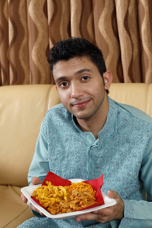 Man holding a plate of Indian snacks