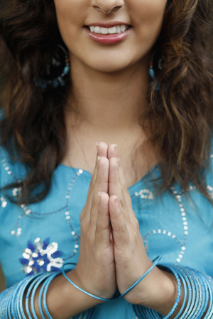 Woman with hands clasped, smiling Stock Photo