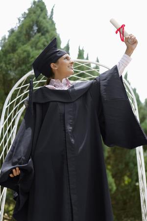 birrete de graduacion: Mujer en traje de graduaci�n de mirarla de desplazamiento LANG_EVOIMAGES