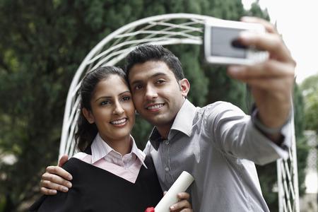toga graduacion: Hombre que toma la foto con la mujer en traje de graduaci�n
