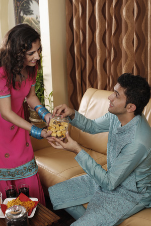 salwar: Woman offering man a jar of cookies LANG_EVOIMAGES