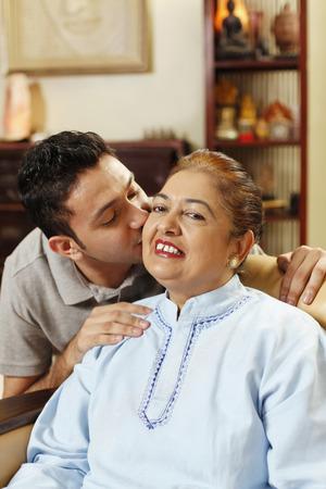 peck: Man giving senior woman a peck on the cheek