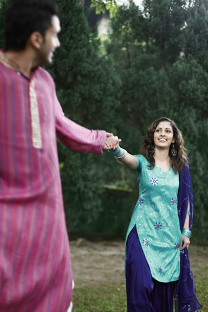 salwar: Man and woman holding hands while walking in the park