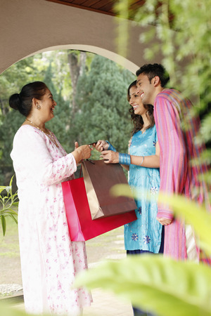 salwar: Woman giving senior woman some gifts, man smiling LANG_EVOIMAGES