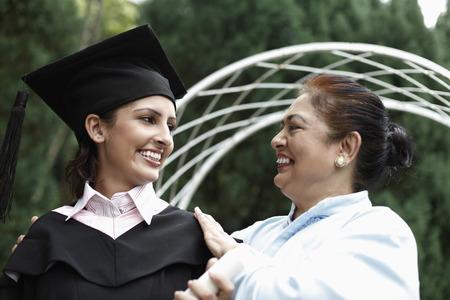 birrete de graduacion: Superior de la mujer y de la mujer en traje de graduaci�n sonriendo el uno al otro