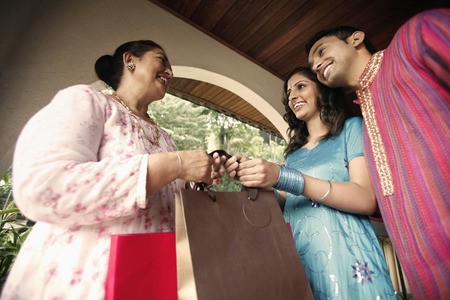 salwar: Man and woman giving senior woman some gifts LANG_EVOIMAGES