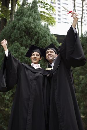birrete de graduacion: Hombre y mujer en traje de graduaci�n celebrar su logro LANG_EVOIMAGES