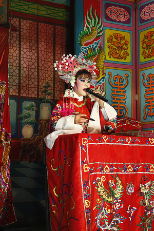 one mature woman only: Opera performer sitting at the altar table holding microphone and paintbrush LANG_EVOIMAGES