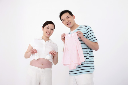 two people fertility: Pregnant woman holding baby shoes while man is holding baby girl clothing
