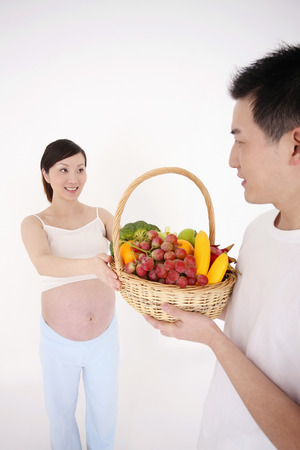 two people fertility: Man giving a basket of fruits and vegetables to pregnant woman