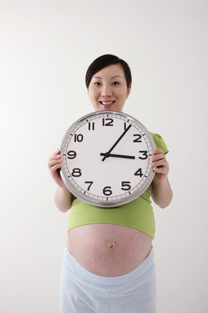 contentment: Pregnant woman holding a clock