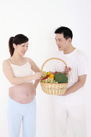 Man carrying a basket of fruits and vegetables, pregnant woman taking a green apple LANG_EVOIMAGES