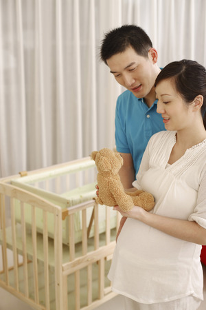 two people fertility: Pregnant woman holding teddy bear, man standing beside her