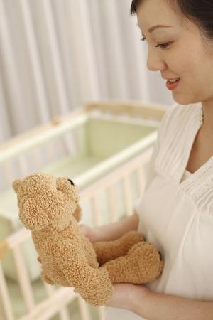 human fertility: Pregnant woman holding teddy bear LANG_EVOIMAGES