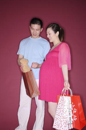 two people fertility: Man showing pregnant woman a teddy bear