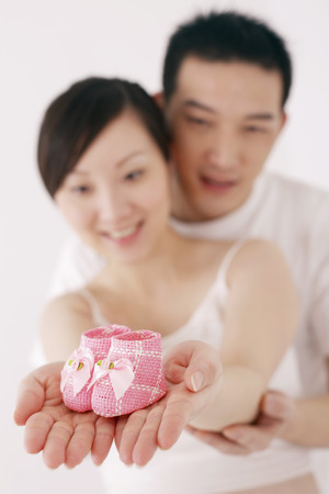 two people fertility: Pregnant woman holding baby shoes, man hugging her from behind LANG_EVOIMAGES