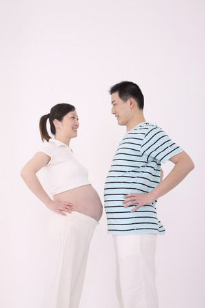 two people fertility: Pregnant woman and man comparing stomachs LANG_EVOIMAGES