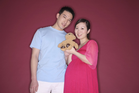 two people fertility: Pregnant woman holding teddy bear, man smiling beside her LANG_EVOIMAGES