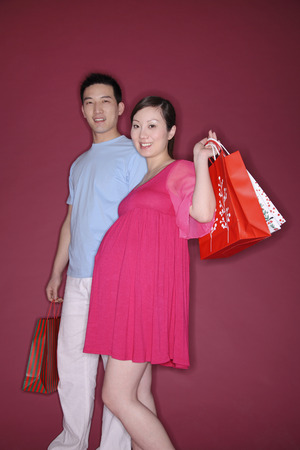 two people fertility: Pregnant woman and man holding shopping bags