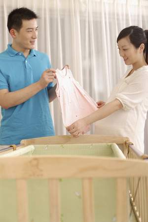 two people fertility: Man and pregnant woman looking at baby girl clothing