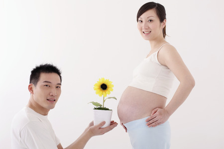 two people fertility: Man holding potted plant in front of pregnant womans stomach