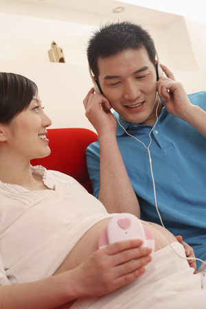 sensory perception: Man listening to music with pregnant woman by his side LANG_EVOIMAGES